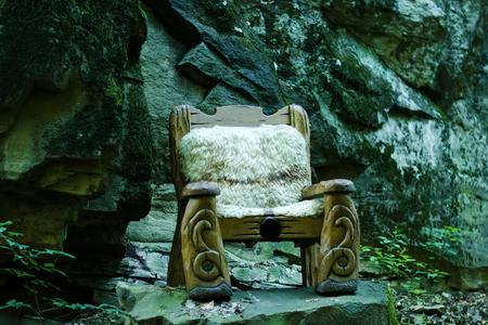 silla de madera: Un corte de madera preciosa sillón grande como reina de los bosques de cuento trono de pie en madera sin gente al aire libre en el fondo de piedra natural gris, horizontal de la imagen
