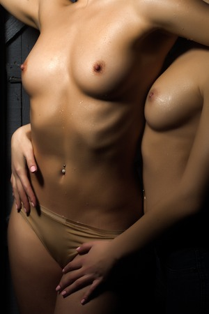 having sex: Closeup of young sexy female naked couple of two lesbian touching and embracing each other having sex with straight beautiful wet body undressed breast and nipples standing close indoor, vertical Stock Photo