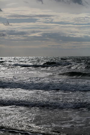 murky: Photo closeup of dramatic grey sea ocean water waves ripples small storm with splashes white spindrifts spoondrifts in dull murky day over seascape background, vertical picture
