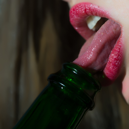 Closeup view of female facial body part of lips with bright red lipgloss licking with tongue in open mouth green color glass wine bottle on blurred background, square picture Imagens