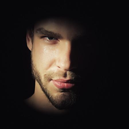 Vue en gros plan d'un beau portrait de jeune homme barbu macho avec de fortes yeux regard noisette et lèvres sexy debout dans la lumière hâte en studio sur fond noir, image carrée Banque d'images - 50347134