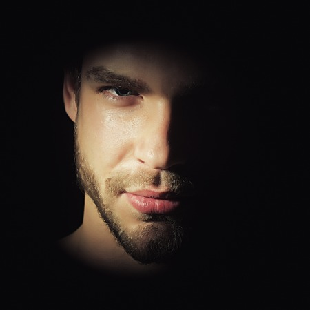Closeup view portrait of one handsome bearded young macho man with strong look hazel eyes and sexy lips standing in light looking forward in studio on black background, square picture