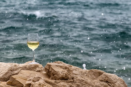 half full: Photo closeup of one half full tall wine glass standing on stone at seashore in splashes spindrifts silhouetted against blue sea at day time over blurred seascape background, horizontal picture Stock Photo