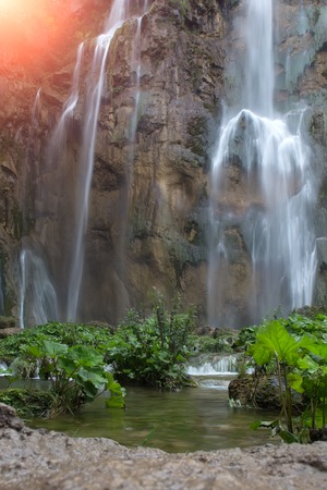 falling down: Photo with sun spot of beautiful waterfalls cascades falling down from mountain wall rock surrounded by picturesque green rich foliage on natural landscape background, vertical picture Stock Photo