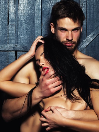 Young sexual undressed sensual attractive couple of handsome bearded muscular macho man touching and embracing passionate pretty woman with body and breast on studio background, vertical picture Stock Photo