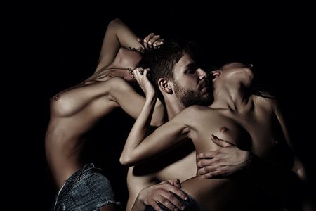 Three young sexy people of handsome bearded muscular macho man touching two sensual attractive girls lovers with beautiful body and naked chest close to each other indoor, horizontal picture