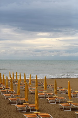 lounges: Photo closeup of sea beach with shut yellow sun umbrellas and orange chaise lounges standing in line on beige sand against cloudy sky murky day bad weather on seascape background, vertical picture