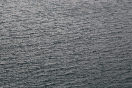 murky: Photo of ripples lippers rips cats-paws on surface of sea ocean water on dull murky day on grey background, horizontal picture