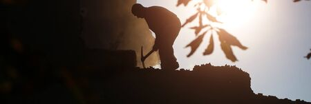light duty: Panoramic image of dark silhouette of labor man digging by pick axe manual equipment heavy male job industrial handcraft on background of light sunbeam outdoor, horizontal picture Stock Photo