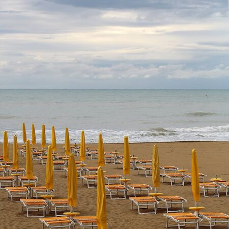 lounges: Photo closeup of sea beach with shut yellow sun umbrellas and orange chaise lounges standing in line on beige sand against cloudy sky murky day bad weather on seascape background, square picture Stock Photo