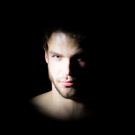 Retrato de vista de detalle de un hombre macho barbudo guapo joven con ojos de avellana mirada fuerte y sexy labios de pie en la luz mirando hacia adelante en el estudio sobre fondo negro, cuadro cuadrado