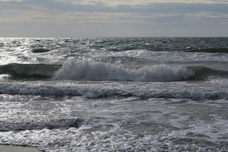 seaway: Photo closeup of dramatic grey sea ocean water waves ripples small storm with splashes white spindrifts spoondrifts in dull murky day over seascape background, horizontal picture Stock Photo