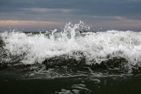 granola: Foto de cerca de romper impresionante cresta de la ola de peine rizador de tormenta top grande con salpicaduras blancas spindrifts spoondrifts de mar gris clara contra el cielo nublado en el fondo marino, cuadro horizontal