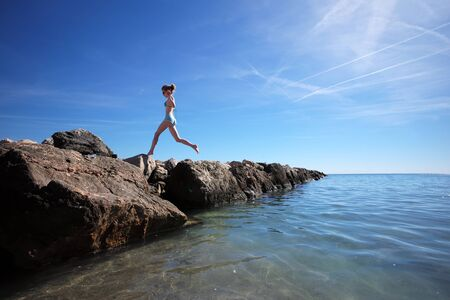 the one person: Photo closeup of one person young girl exercising jumping on wet stones at seashore with clear sea water against bright blue sky summer time on seascape background, horizontal picture
