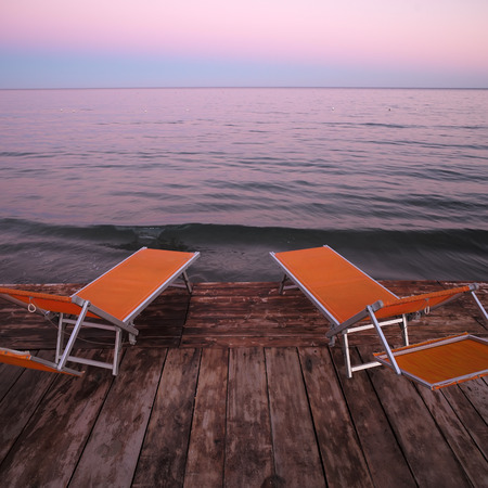 lounges: Photo closeup of two orange chaise lounges day beds couches standing on wooden pier against rose blue sunset light on peaceful seascape background, square photo