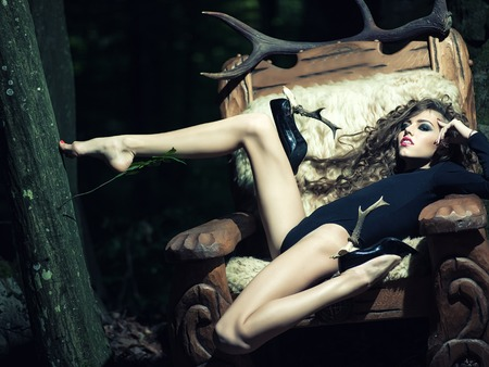 One beautiful young flexible sensual girl with long curly hair bright makeup and straing slim body in black underwear and shoes with heel of antlers sitting in big wooden arm chir with fur in forest Stock Photo
