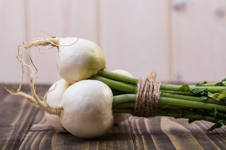 dikon: Ripe raw crude white round daikon with greens in bundle connected with twine on brown wooden table on white wall background, horizontal picture