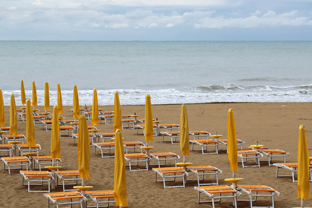 lounges: Photo closeup of sea beach with shut yellow sun umbrellas and orange chaise lounges standing in line on beige sand against cloudy sky murky day bad weather on seascape background, horizontal picture