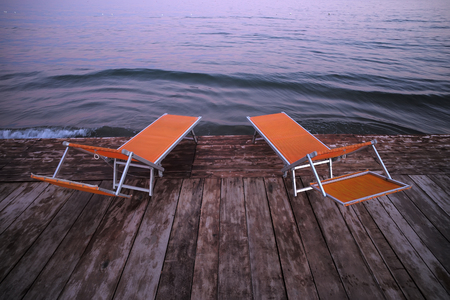lounges: Photo closeup of two orange chaise lounges day beds couches standing on wooden pier against rose blue sunset light on peaceful seascape background, horizontal photo Stock Photo