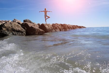 the one person: Photo closeup with sun spot of one person young girl exercising lifting leg and hands on wet stone at seashore with blue waves and white spindrifts running on seascape background, horizontal picture Stock Photo