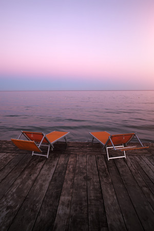 lounges: Photo closeup of two orange chaise lounges day beds couches standing on wooden pier against rose blue sunset light on peaceful seascape background, vertical photo