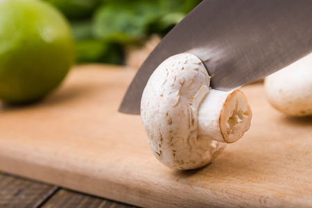 potherbs: Closeup photo of knife cutting fresh crude champignon on wooden board with vegetables and potherbs on table, horizontal picture