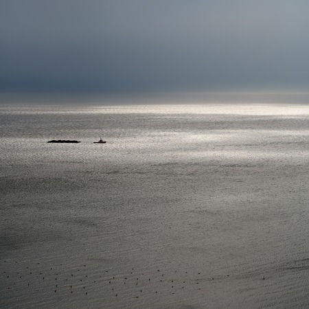 grey  sky: Photo of tug boat on spectacular maritime seashore and sea with ripples low waves against dark grey sky at dull murky day over seascape background, square picture