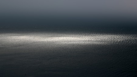 desolaci�n: Photo of spectacular dark marine seashore sea horizon with ripples fuses with grey sky at dusk bleakness over seascape background, horizontal picture