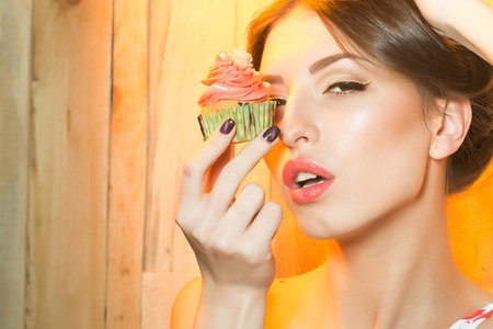Closeup view portrait of one beautiful sensual young woman with makeup and bare shoulders near tasty fresh homemade cup cake with orange cream with flower icing in green paper indoor, horizontal photo Reklamní fotografie