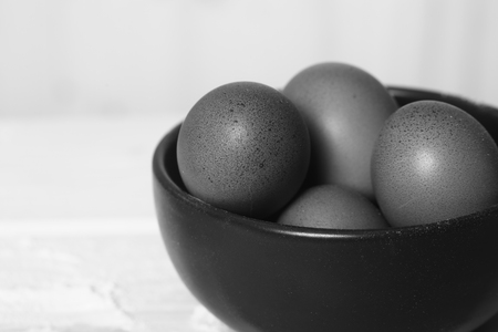 duckboards: Closeup view of clay plate full of many raw whole brown chicken eggs in kitchen for preparing fresh homemade food indoor on blurred background black and white copy space, horizontal picture Stock Photo