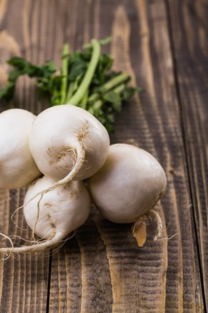 Bunch of raw white round turnips daikon with green stem on brown wooden table, vertical picture