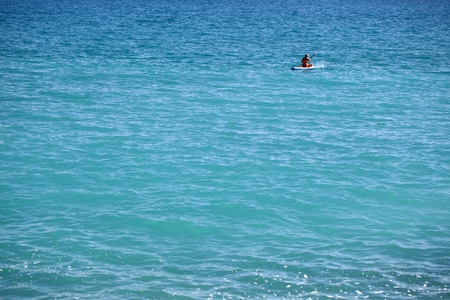 plan �loign�: Photo long shot of beautiful panoramic view of bright blue sea waters and woman rowing rubber boat at distance offshore summer time good weather on seascape background, horizontal picture