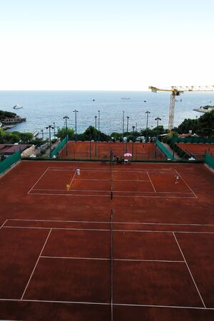 plan éloigné: Photo long shot beautiful view from height to many lawn tennis courts peaceful marine clear blue sky on seascape background, vertical picture