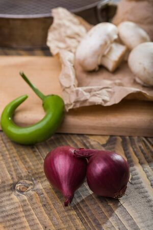 Sweet purple onions shallot with white champignons on paper green chili pepper on cutting board on wooden table, vertical photo