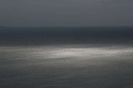 desolaci�n: Foto de la espectacular costa marina horizonte marino oscuro con ondulaciones contra el cielo gris en la oscuridad intemperie sobre el fondo marino, cuadro horizontal Foto de archivo