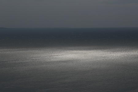 seascape: Photo of spectacular dark marine seashore sea horizon with ripples  against grey sky at dusk bleakness over seascape background, horizontal picture Stock Photo