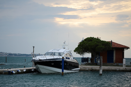 murky: Photo closeup of one beautiful modern yacht at moorage at boat landing pier maritime terminal small cottage green tree against murky cloudy sky on seascape background, horizontal picture