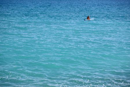 plan �loign�: Photo long shot de la belle vue panoramique sur les eaux bleu clair de la mer et femme bateau � rames de caoutchouc � une distance l'heure d'�t� au large des c�tes du beau temps sur seascape fond, image horizontale Banque d'images