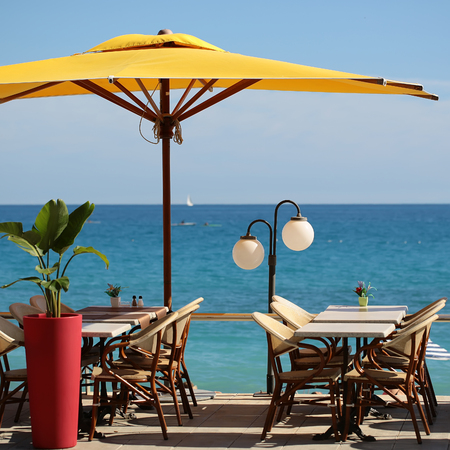 sun umbrella: Photo closeup of beach cafe big yellow sun umbrella tables and chairs in rows green plant in red flower pot white street lamp on blurred blue seascape background, square picture