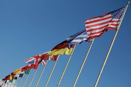 flutter: Photo long shot of different national flags flutter in wind on tall flagstaffs in rows against bright blue sky background, horizontal picture Stock Photo
