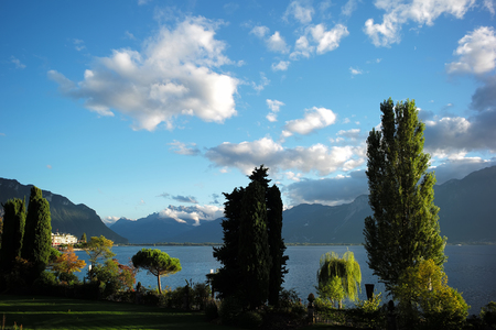 long shot: Photo long shot of picturesque summer landscape of peaceful day at lake shore waterside green trees high mountains white clouds on bright blue sky background, horizontal picture