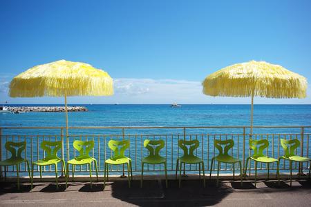 Foto Nahaufnahme von zwei gelben Sonnenschirme für den Sonnenschutz und hellgrünen Kunststoff-Stühle in Linie an der Küste Silhouette gegen den strahlend blauen Himmel und Meer auf Meereslandschaft Hintergrund, horizontale Bild