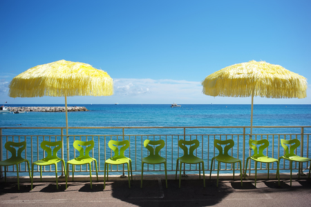 sun protection: Photo closeup of two yellow beach umbrellas for sun protection and light green plastic chairs in line at seashore silhouetted against bright blue sky and sea on seascape background, horizontal picture