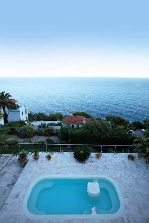 long shot: Photo long shot beautiful view from height to swimming pool cottage yard green trees palm peaceful marine clear blue sky on seascape background, vertical picture