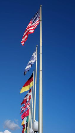 flutter: Photo long shot of different national flags flutter in wind on tall flagstaffs in rows against bright blue sky background, vertical picture Stock Photo