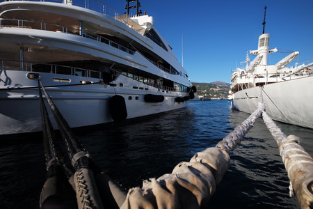 blue vessels: Photo closeup of beautiful modern white ships sea liners yachts vessels at moorage with nautical ropes at seashore clear water on sunny summer day on bright blue sky background, horizontal picture