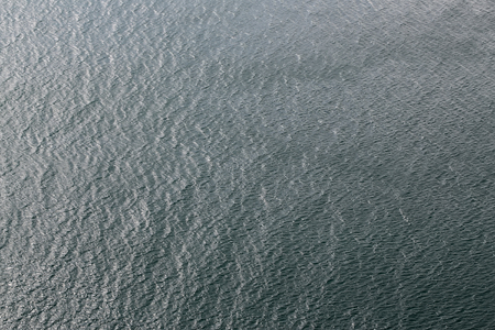 Photo of ripples lippers rips cats-paws on surface of sea ocean water on dull murky day on grey seascape background, horizontal picture