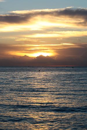desolaci�n: Foto de la espectacular costa del mar mar azul marino con las ondulaciones contra la iluminaci�n de color amarillo-luz del cielo nublado bajo nivel en la oscuridad intemperie hora del atardecer sobre el fondo marino, imagen vertical