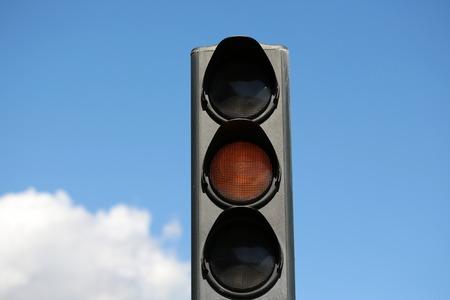 Photo closeup traffic light semaphore with yellow light-signal caution indicator signaling device day time against blue sky background, horizontal photo Imagens - 50694340
