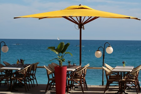 sun umbrella: Photo closeup of beach cafe big yellow sun umbrella tables and chairs in rows green plant in red flower pot white street lamp on blurred blue seascape background, horizontal picture